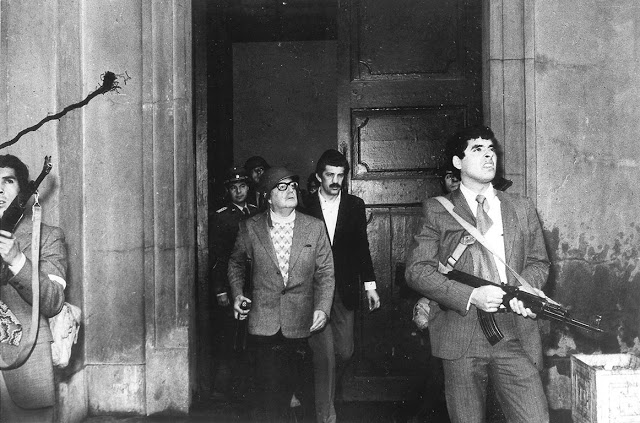 Chilean President Salvador Allende, flanked by body guards during the coup on 11 September 1973. Later that day, Allende was reported dead.